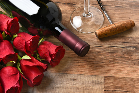 glass of red wine: A wine bottle with red roses and a glass and cork screw on a rustic wood table.