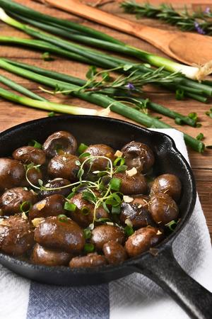 cebollas: Alto ángulo de visión vertical de setas salteadas en una sartén de hierro fundido rodeado de ingredientes y utensilios.