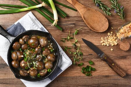 mushrooms: High angle view of sauteed mushrooms in a cast iron skillet surrounded by ingredients and utensils. Horizontal on a rustic kitchen table. Stock Photo