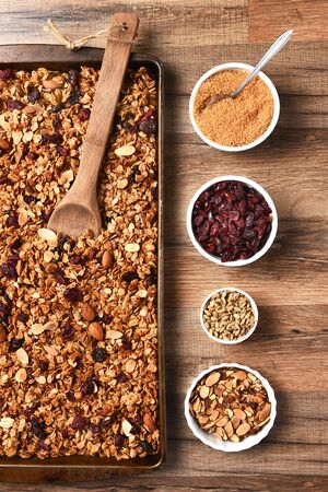 healthful: High angle view of fresh homemade granola. Baking sheet filled with the tasty, healthful food with containers of ingredients.