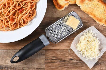 queso rallado: Vista de ángulo alto de una parrilla de queso con queso parmesano en una mesa de cocina de madera rústica. Un plato de espaguetis y pan de ajo también se muestran. Foto de archivo