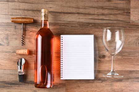 cork screw: A high angle view of a wine bottle tasting notes notebook, cork screw, and wine glass on a wood table. Stock Photo