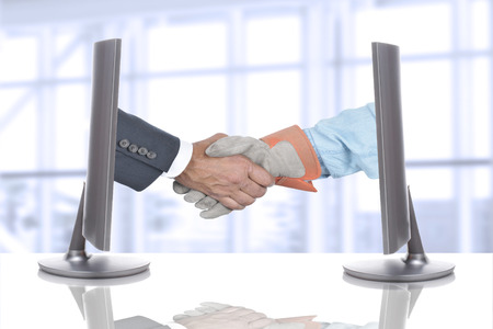 hands out: Handshake Over Desk in Business Office. Both hands are coming out of computer screens.