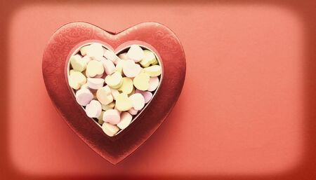 high angle shot: A high angle shot of candy valentines on top of another heart shaped box. Horizontal format with a vintage, faded instagram look and intentional vignette. Stock Photo