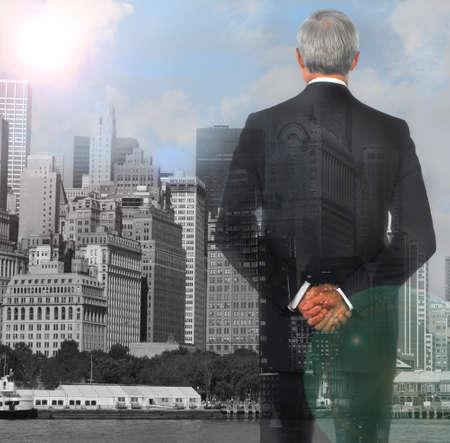 exposicion: El hombre de negocios doble exposición con las manos cruzadas a la espalda con el fondo de la ciudad y reflejo en la lente.