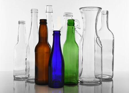 Les bouteilles en verre vides sur fond blanc avec la réflexion. Verre et bouteilles colorées.