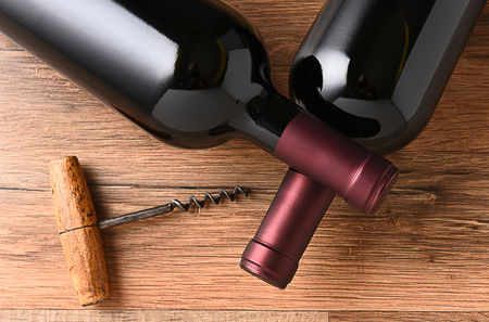 cork screw: Top view of two wine bottles with their necks crossed and and old fashioned cork screw.