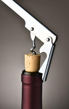 cork   screw: Closeup of a modern metal cork screw pulling the cork from a wine bottle.