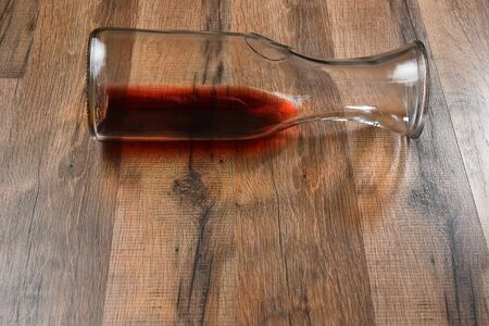 carafe: High angle view of a carafe of wine on its side on a wood table.