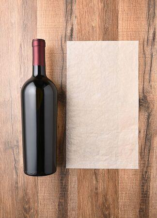 Vista superior de una botella de vino junto a una hoja de papel en blanco. Lista de vino concepto.