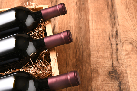 high angle: High angle view of a crate of wine bottles on a wood table with copy space.