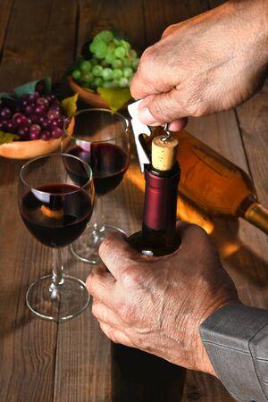 chrome man: Closeup of a man opening a wine bottle.