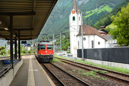 railway transportation: FLUELEN, SWITZERLAND - JULY 4, 2014: Train Platform. A train comes in at the platform in Fluelen, Switzerland, on Lake Lucern.