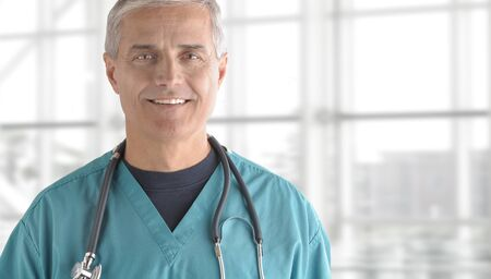 50 to 60: Portrait of smiling senior doctor standing against office window background while looking at camera.