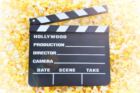 black boards: top view of a movie clapperboard on a field of popcorn with lens flare effect. Stock Photo