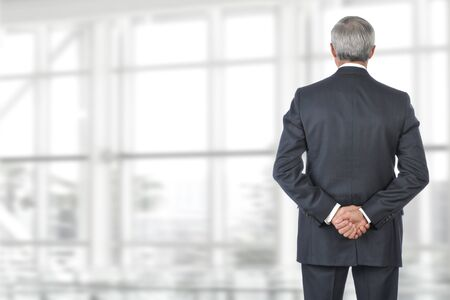 clasped hand: Portrait of smiling senior businessman standing looking out of office window with his hand behind his back. Stock Photo