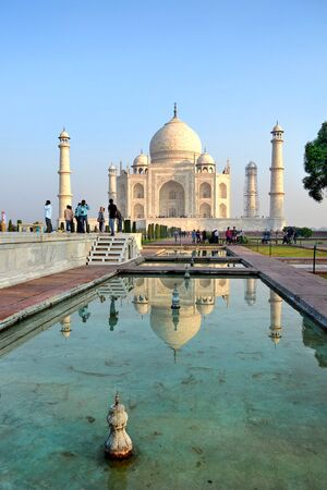 mughal architecture: AGRA, INDIA - 31 OCTOBER 2015: Tourists at the Taj Mahal. The temple is reflected in one of the the ponda. Editorial