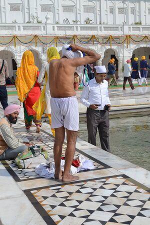 personas banandose: AMRITSAR, INDIA - 30 de octubre de 2015: Las personas que se ba�an en el lago en el templo de oro (Harmandir Sahib) de Amritsar, Punjab, India, el gurdwara sij m�s sagrado del mundo.