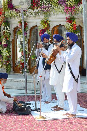 gurdwara: AMRITSAR, INDIA - 30 OCTOBER 2015: Sikh Musicians perform at the Golden Temple. Sri Harmandir Sahib (The Abode of God) is the holiest Sikh gurdwara.