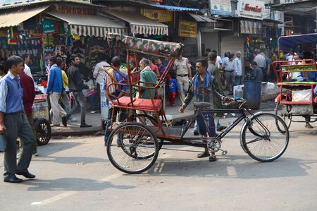 new delhi: NEW DELHI, INDIA - OCTOBER 27, 2015: Crowded street scene in New Delhi with pedicab. Pedicabs are a source of income for many people in Asia. Editorial