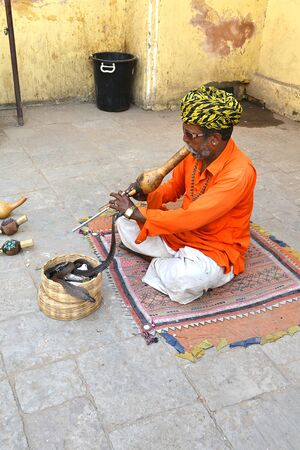 charmer: JAIPUR, INDIA - NOVEMBER 2, 2015: Snake charmer. Man plays his pungi to charm a cobra outside the Jantar Mantar monuments in India.