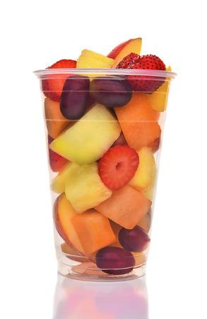 Een plastic beker van vers gesneden fruit. Geïsoleerd op wit met reflectie, vruchten bevatten aardbei, ananas, appel, Cantaloupe, honingdauw en druiven.