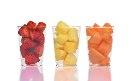 Three fresh fruit cups on white with reflection. Strawberries, Pineapple and Cantaloupe in plastic cups.