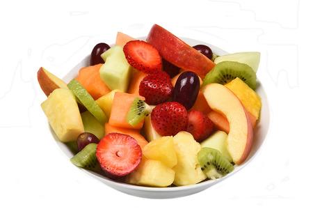 신선한 잘라 과일의 그릇. 흰색 과일에 고립, 딸기, 파인애플, 사과, 멜론, 허니 듀 멜론, 키위, 포도 등이 있습니다.