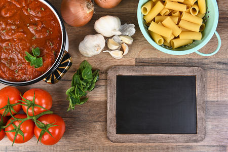 horizontal format: Top view of ingredients for an Italian Meal. Horizontal format with a blank chalkboard. Stock Photo