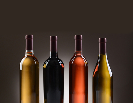 cabernet sauvignon: Closeup of four wine bottles with no labels on a light to dark gray background.