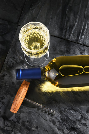 cork screw: Top View of a white wine bottle laying on its side on black slate. Vertical format with cork screw and wine glass, with copy space.