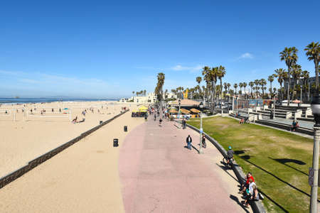huntington beach: HUNTINGTON BEACH, CA - MARCH 25, 2015: Boardwalk and Sand Volleyball Courts. The boardwalk, near the pier, accommodates strollers, skaters and bicycles.