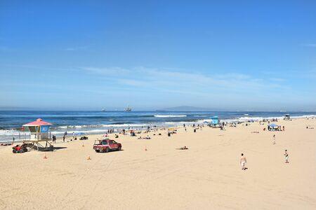 huntington beach: HUNTINGTON BEACH, CA - MARCH 25, 2015: Huntington Beach Shoreline with lifeguard stations and beach goers on a sunny Spring day.