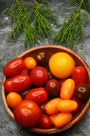 medley: Top view of a bowl of fresh picked Medley Tomatoes on a slate surface. Vertical Format. Stock Photo