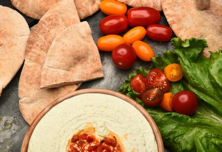 medley: Top view of pita bread, edamame hummus, and medley tomatoes on a slate table.