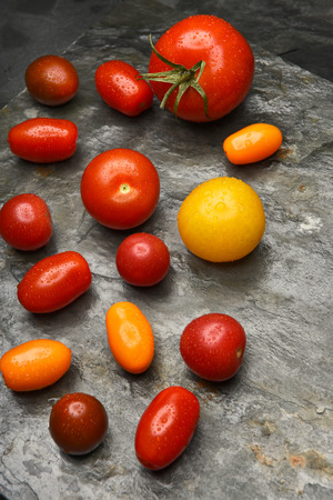 medley: Top view of a group of medley tomatoes on a slate table. Stock Photo