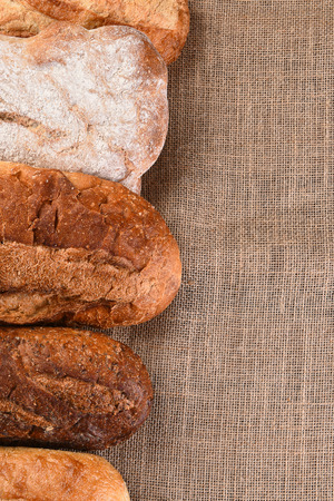 vertical format: Five different loaves of bread on a wood table with copy space. Vertical format.