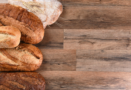 horizontal format: Five different loaves of bread on a wood table with copy space. Horizontal format.