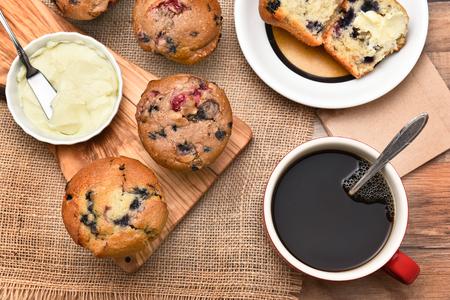 colazione: Vista dall'alto di un tavolo da colazione con muffin assortiti, caffè e burro. Gli oggetti sono su una tavola di legno con panno di tovaglia.