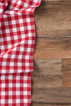 vertical format: Red and white checkered table cloth on a wood table with copy space, vertical format.