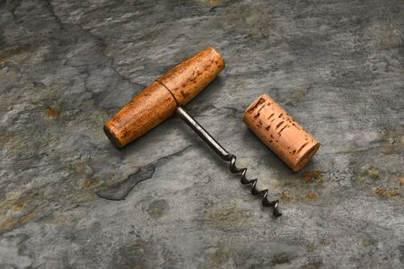 cork screw: Top view of an old fashioned cork screw and cork on a slate background. Stock Photo