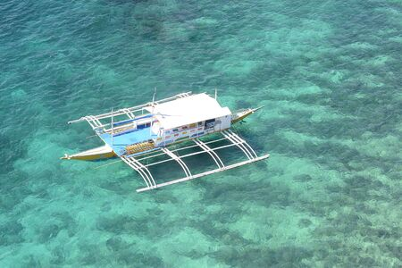 waters: BOHOL, PHILIPPINES - APRIL 5, 2016:  Outrigger anchored in the blue-green tropical waters off the coast of Bohol in the Philippines. Editorial