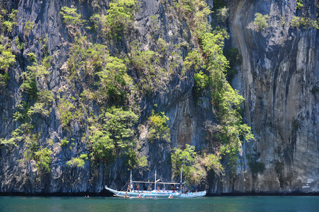 palawan: EL NIDO, PALAWAN, PHILIPPINES - APRIL 5, 2016:  Pleasure boat with tourists swimming in the waters off of El Nido Island in the Philippines.