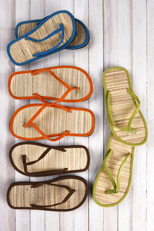 high angle view: High angle view of a group of beach sandals on a white wood deck, vertical format. Stock Photo