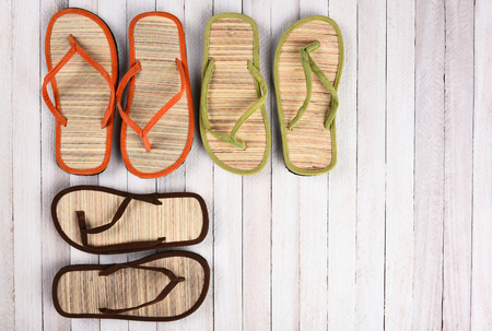 high angle: High angle view of a group of beach sandals on a white wood deck.