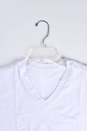 tee shirt: Closeup of a white tee shirt on a clear plastic hanger. Vertical format.
