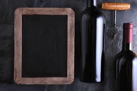 Bovenaanzicht van een lege krijtbord voor een wijnkaart of het menu met twee flessen wijn en oude kurkentrekker. Zijlicht op een lei tafel.