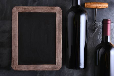 cork screw: Top view of a blank chalk board for a wine list or menu with two wine bottles and old cork screw. Side light on a slate table. Stock Photo