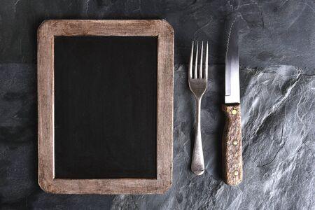 Vista desde arriba de un cuchillo y un tenedor junto a una pizarra en blanco del menú. Una luz lateral potente en una mesa de pizarra de color negro. Foto de archivo - 58488099