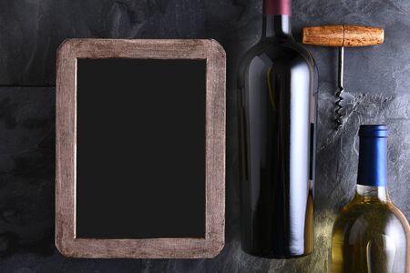 Bovenaanzicht van twee flessen wijn en kurkentrekker naast een lege wijnkaart krijtbord.